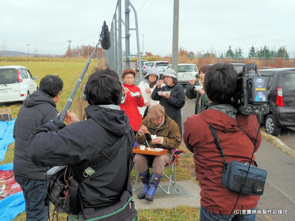 昼食のカレーライスを食べながらインタビューを受ける坪川監督と応援団員